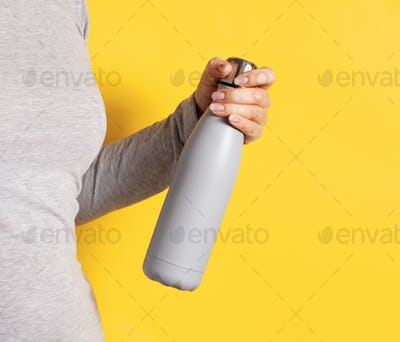 Woman in grey tee holding grey insulated bottle on yellow background