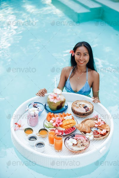 Smiling woman with tanned skin swims in pool with floating table