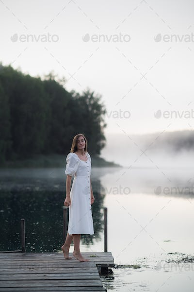Tender romanitc sentimental female lady in the morning on a wooden pier near the misty river in a