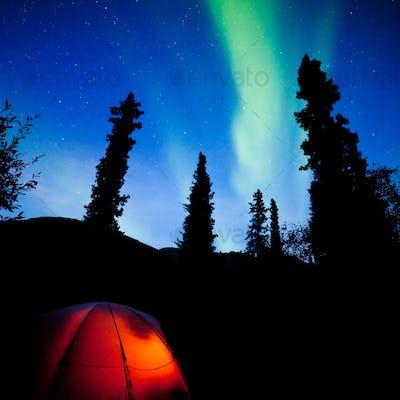 Orange taiga tent glow under northern lights flare