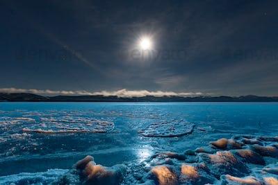 Full moon over frozen Lake Laberge Yukon Canada
