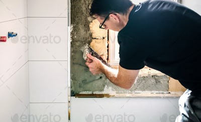 Male mason leveling cement with a trowel