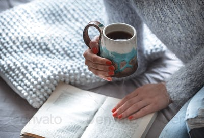 girl holds a cup and reads book