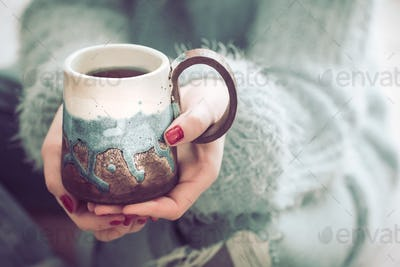 girl holding a cup of tea in hands