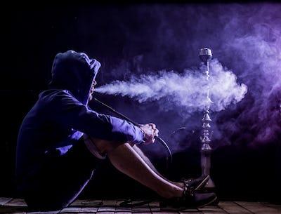 a man smokes a hookah on a black background, beautiful lighting