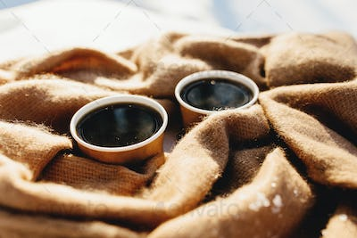 Two cups of coffee on a scarf in the snowy forest
