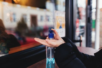 Using of sanitizer before entering the cafe. Blurred background