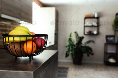 Fruits in fruit bowl on bar counter in stylish loft kitchen. Blurred background