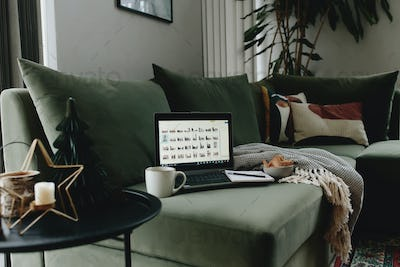 Laptop on the green sofa. Work from home. Loft or modern interior