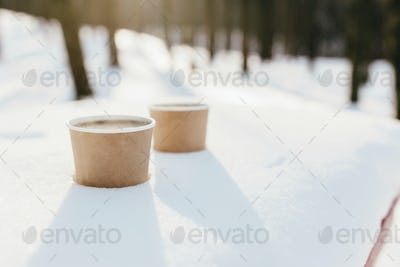 Two cups of coffee in the snow in the forest