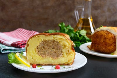 Potato balls with minced meat in deep fat, baked with mozzarella. Cut, close-up