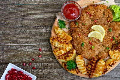 Large schnitzel with baked golden potatoes on a wooden cutting board. Wiener Schnitzel. Top view.
