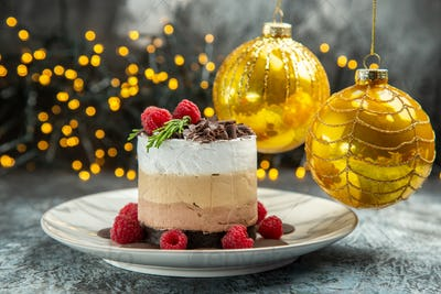 front view cheesecake with chocolate and raspberries on oval plate xmas tree balls xmas lights on