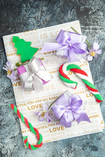 top view colorful xmas gifts flowers xmas candies on newspaper on grey background