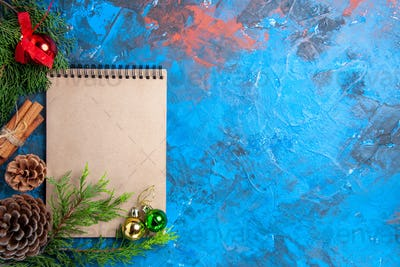 top view xmas tree balls on a notebook pine tree branches pinecone on blue background free space