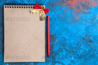 top view a notepad with small bow red pencil on blue background with copy place