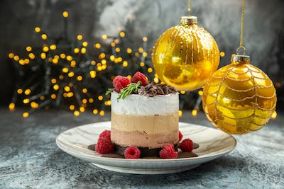 front view cheesecake with chocolate on white oval plate xmas tree balls xmas lights on grey