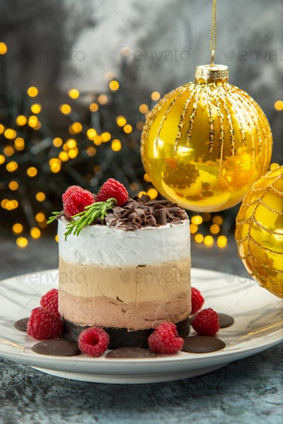 front view cheesecake with chocolate on oval plate xmas tree balls xmas lights on grey background