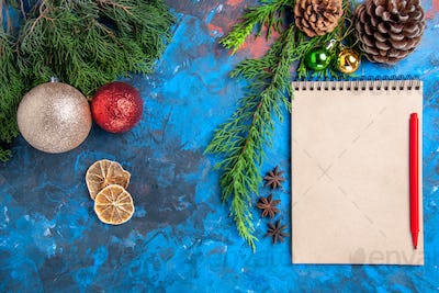 top view red pencil on a notebook pine tree branches dried lemon slices on blue background