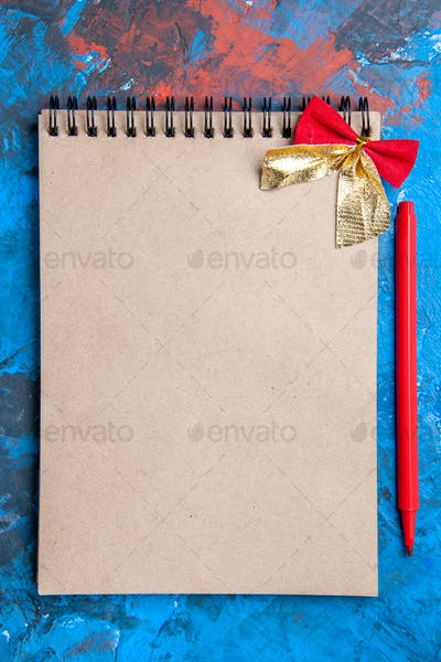 top view a notepad with little bow pencil on blue background