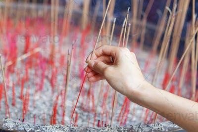 Offering incense stick to god in Chinese temple