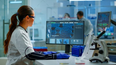 Biologist doctor checking DNA informations typing on pc