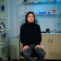 Stressed patient sitting in neurological lab waiting for medical researcher