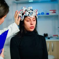 Patient with eeg headset discussing with medical researcher during examination