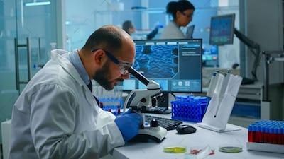 Medical research scientist conducting vaccine development under digital microscope