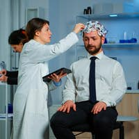Man with brainwave scanning headset visiting professional doctor