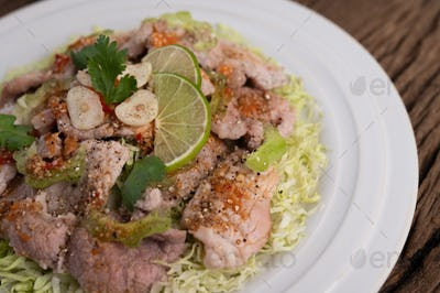 Spicy lime pork salad with galangal, chilli, tomatoes and garlic in a white plate on a wooden floor.