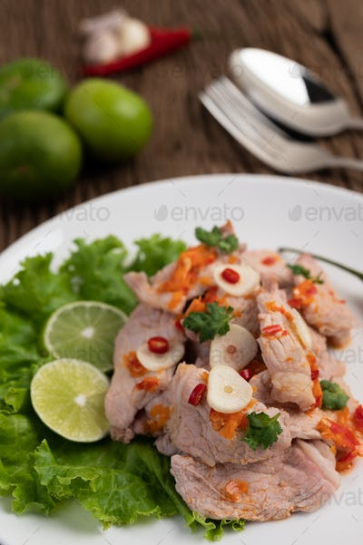 Spicy lime pork with salad, galangal, chilli, tomato and garlic on a white plate on a wooden floor.