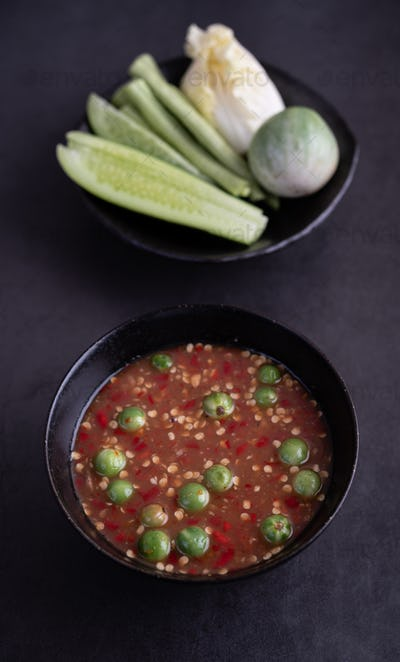 Shrimp-paste sauce in a black bowl on floor cement with Cucumber, yard long beans, Thai eggplant.