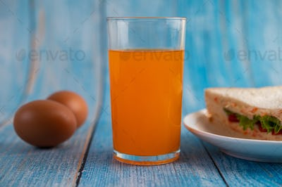 Sandwiches and orange juice on the blue wooden floor.
