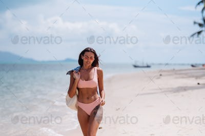 Happy fit pretty tanned sporty tattooed woman travel on tropical beach with backpack