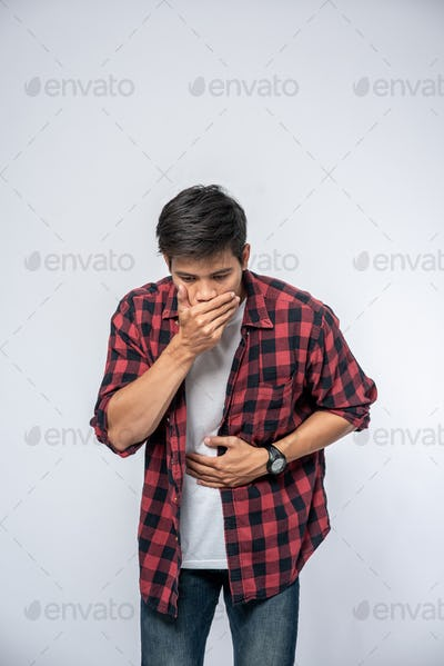 A man standing with a stomachache Put your hands on your stomach and cover your mouth.