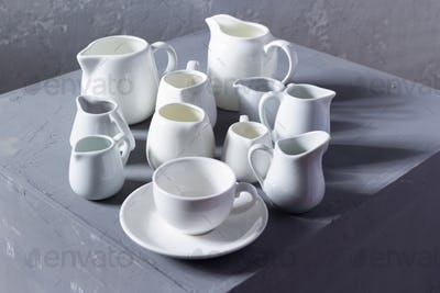 Empty crockery or ceramic dishes set. Kitchen dishware and tableware on grey near wall background