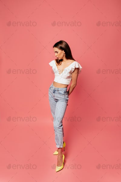 Stylish woman in white top and jeans wearing yellow heels posing over pink background