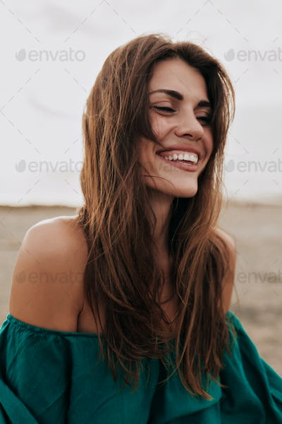 Happy charming model wearing dress with bare shoulders smiling with closed eyes on the beach