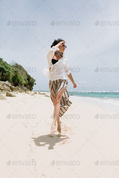 Full-lenght portrait of adorable happy woman jumping on the sandy beach on shore of the ocean