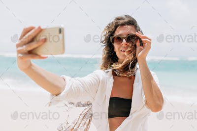 Portrait of attractive brunette woman with long wavy hair posing on shore of the ocean sunset