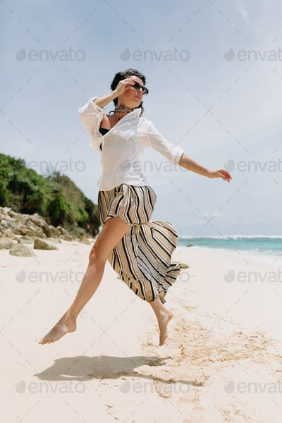 Beautiful woman wears summer outfit jumping on the tropic Beach