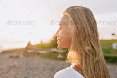 Back view of lovely smiling charming woman with long hair and adorable smile looking on the ocean