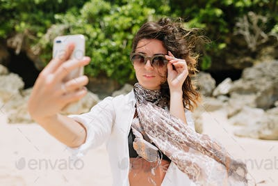 Beautiful stylish model in white shirt and black top is having fun and makes selfie and smile