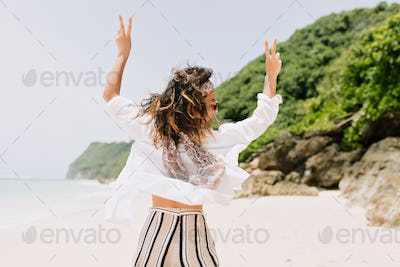 Back view of happy jumping elegant woman with flying hair dressed summer stylish outfit