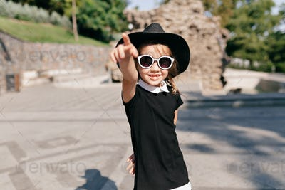 Portrait little girl dressed black dress and hat and sunglasses  finger point destination