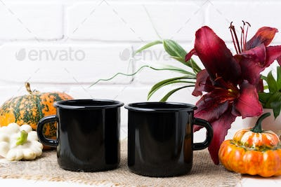 Two black campfire enamel mug mockup with pumpkin and red lily