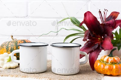 Placeit-Two white campfire enamel mug mockup with pumpkin and lily