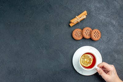 top view a cup of tea with lemon cinnamon sticks cookies on dark background with copy space