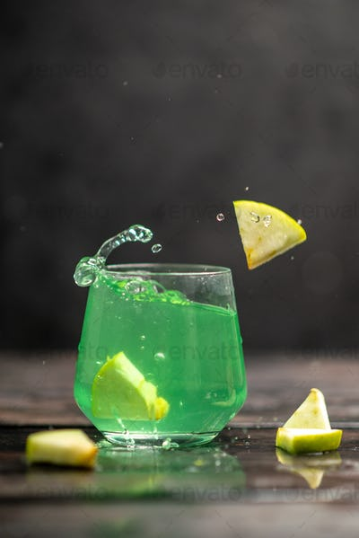 Vertical view of delicious juice in a glass with apple limes in i on dark background